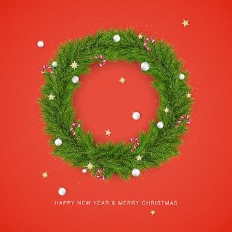 Wesołych świąt i szczęśliwego nowego roku. wieniec choinkowy ozdobiony bombkami i cukierkami. element dekoracji wakacje na czerwonym tle.