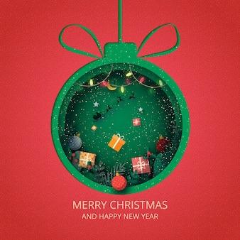 Wesołych świąt i szczęśliwego nowego roku. zielona bombka ozdobiona pudełkiem i mikołajem w saniach.