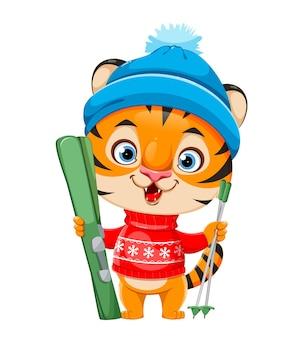 Wesołych świąt. kreskówka postać tygrysa w ciepłym kapeluszu stojący z nartami. stockowa ilustracja wektorowa na białym tle.
