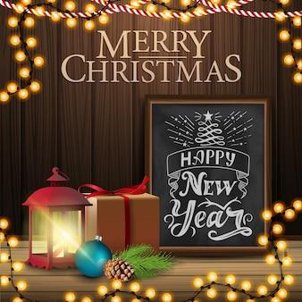 Wesołych świąt, kwadratowa pocztówka z prezentem, antyczna lampa, gałąź choinki, stożek, bombka