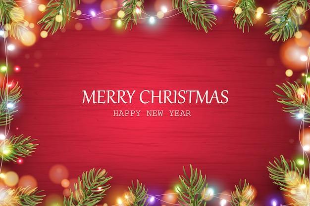 Wesołych świąt. szczęśliwego nowego roku. bożenarodzeniowy czerwony drewniany tło z wakacyjnymi jedlinowymi gałąź, sosna rożek, błyszcząca lekka girlanda, bokeh.