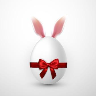 Wesołych świąt wielkanocnych jajko z czerwoną kokardką i uszami zajączka
