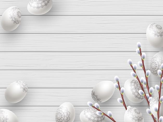 Wesołych świąt wielkanocnych skład pisanki i gałązki wierzby na białym drewnianym.
