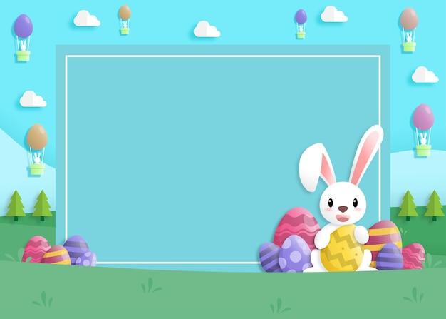 Wesołych świąt wielkanocnych w stylu papierowej sztuki z królikiem i pisankami.