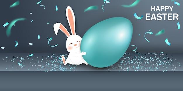 Wesołych świąt wielkanocnych. wielkanocny królik z realistycznym niebieskim jajkiem na szarym tle. ładny, zabawny kreskówka królik z jajkiem paschalnym.