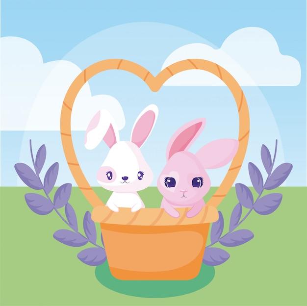 Wesołych świąt wielkanocnych z uroczymi królikami w koszu i ozdobnym wieńcem