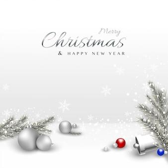 Wesołych świąt z bombkami i liśćmi sosny pokrytymi śniegiem