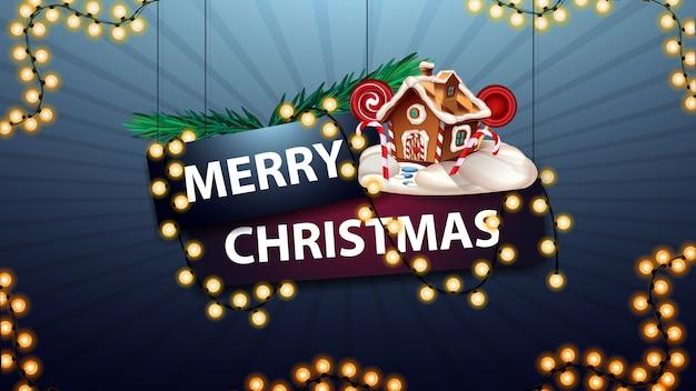 Wesołych świąt, znak owinięty girlandą z gałęziami choinki i świątecznym domkiem z piernika