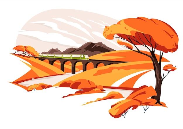 Wiadukt kolejowy wśród jesiennych żółtych wzgórz łąki z górami pomarańczowy pociąg dzika przyroda trawa co