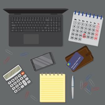 Widok ciemnego biurka, w tym laptopa, urządzeń cyfrowych, obiektów finansowych i biznesowych.
