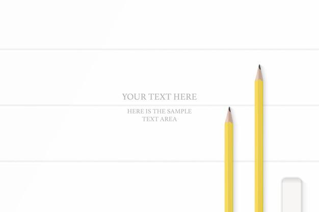 Widok z góry elegancka biała kompozycja żółte ołówki gumka na tle drewnianej podłogi.
