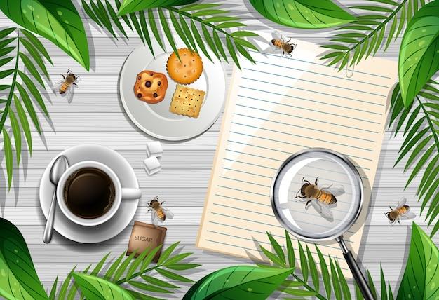 Widok z góry na drewniany stół z obiektami biurowymi oraz elementem liści i owadów