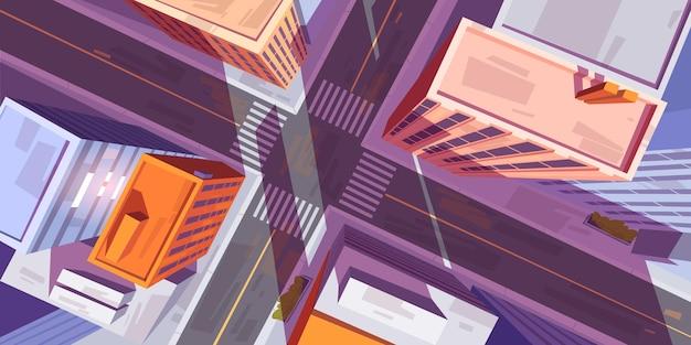 Widok z góry na miasto z budynkami i skrzyżowaniem dróg samochodowych z przejściem dla pieszych.