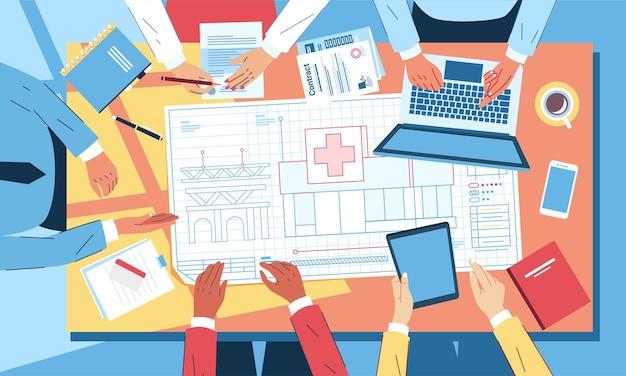 Widok z góry planu office meeting for construction, na biurku jest niebieski druk budynku, laptop, tablet
