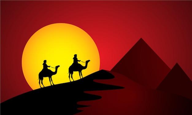 Wielbłądy w zachód słońca pustyni