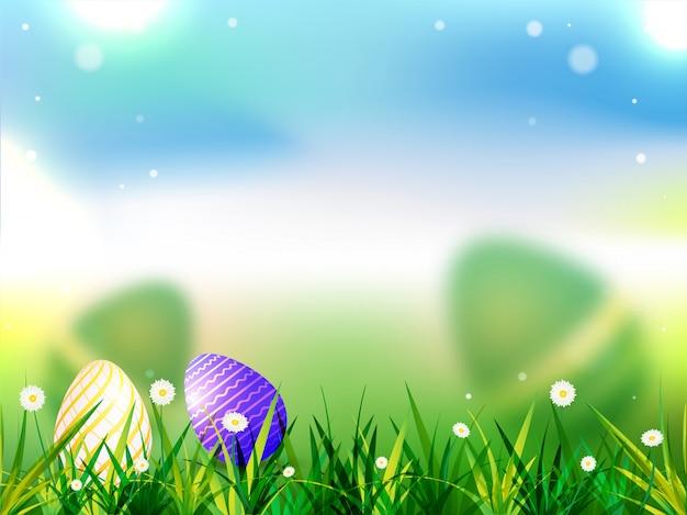 Wielkanocni jajka chujący w trawie na zamazanym tle