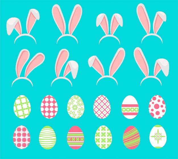 Wielkanocni jajka z zajęczymi ucho ustawiającymi na białym tle.