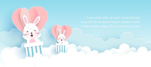Wielkanocny baner z słodkie króliki i pisanki w stylu cięcia papieru i rzemiosła.