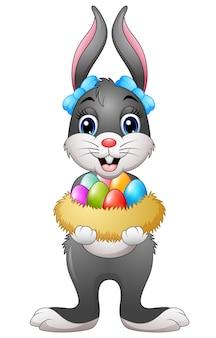 Wielkanocny królik trzyma easter jajka w gniazdeczku
