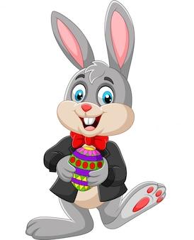 Wielkanocny królik trzyma wielkanocnego jajko
