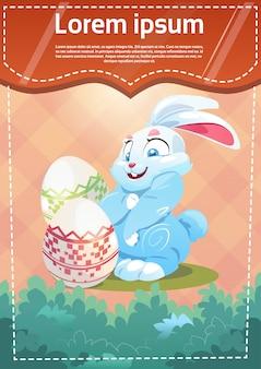 Wielkanocny królik trzymający dekorujący kolorowy jajeczny wakacyjny symbol kartka z pozdrowieniami