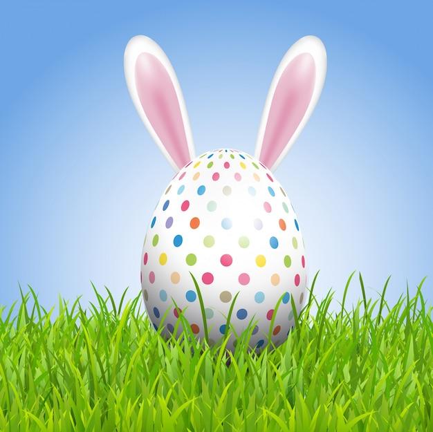Wielkanocny tło z królików ucho i jajko w trawie