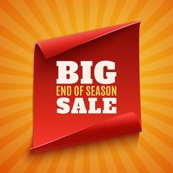 Wielki plakat wyprzedaży na koniec sezonu. czerwony, zakrzywiony, papierowy baner na pomarańczowym tle z promieniami świetlnymi.