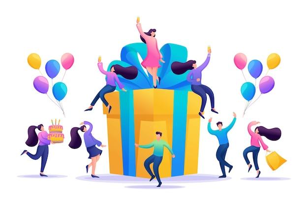 Wielkie przyjęcie urodzinowe z przyjaciółmi. ludzie świętują, piją szampana i bawią się wielkim prezentem.