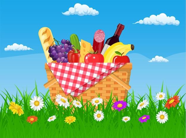 Wiklinowy kosz piknikowy pełen produktów. wino, kiełbasa, bekon i ser, jabłko, pomidor, ogórek. trawa, kwiaty, niebo z chmurami.