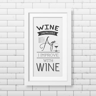 Wino poprawia się z wiekiem, ja poprawiam się z winem - cytuj typograficzny w realistycznej kwadratowej białej ramce na ścianie z cegły