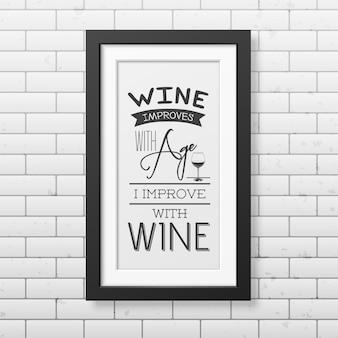 Wino poprawia się z wiekiem, ja poprawiam się z winem - typograficzny cytat w realistycznej kwadratowej czarnej ramce na murze