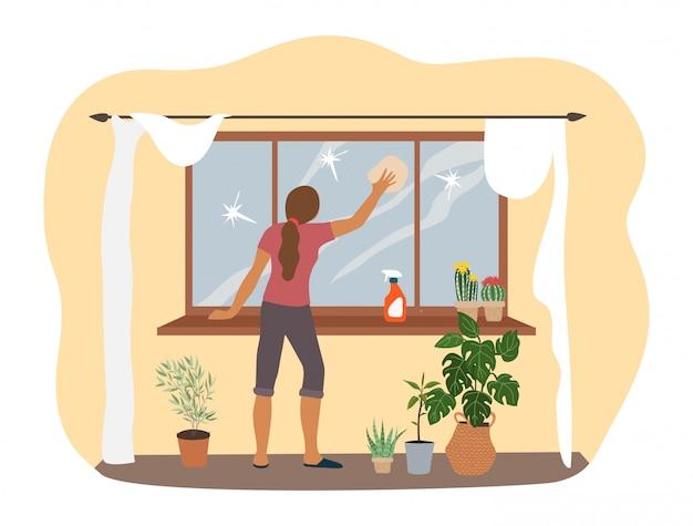 Wiosenne porządki w domu, kobieta myje okno w mieszkaniu.