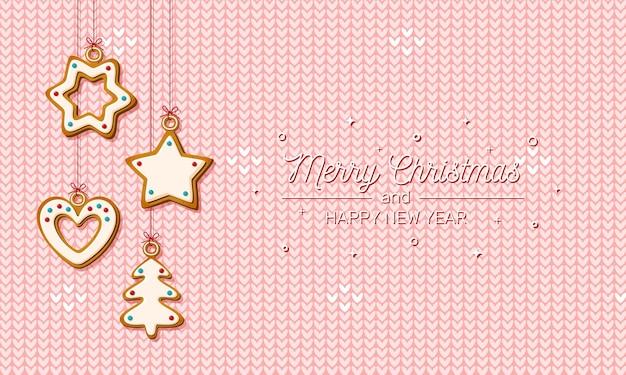 Wiszące świąteczne pierniki na różowym tle z dzianiny. świąteczne ciasteczka w kształcie domu i choinki, gwiazdy i płatka śniegu oraz serca na świąteczną kartkę z życzeniami. ilustracja wektorowa