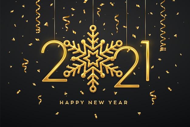 Wiszące złote metaliczne cyfry 2021 z błyszczącym płatkiem śniegu i konfetti na czarnym tle.