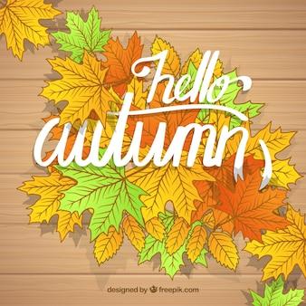 Witam jesienią, drewnianym stołem z liśćmi