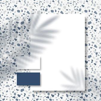 Wizytówki i papier firmowy na powierzchni lastryko z nakładką w cieniu tropikalnych liści palmowych