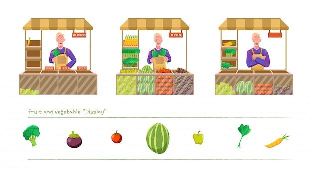 Właściciel sklepu z warzywami z wózkiem na warzywa i eksponatami na warzywa i owoce