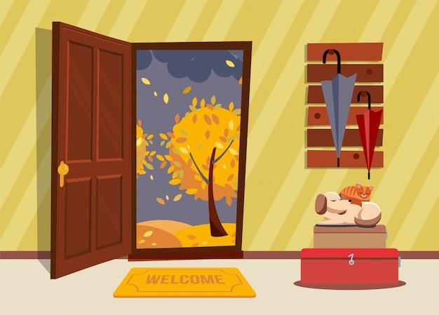 Wnętrze przedpokoju z otwartymi drzwiami, wieszakiem z parasolami i śpiącym psem oraz kotem na walizkach.