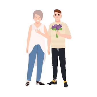 Wnuk daje babci bukiet kwiatów. młody nastoletni chłopak gratulując radosnej starszej kobiety. dziadek i wnuk obchodzą urodziny