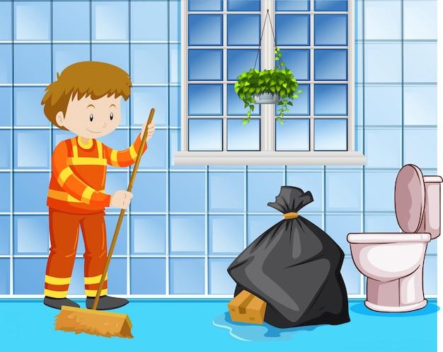Woźny czyści mokrą podłogę w toalecie