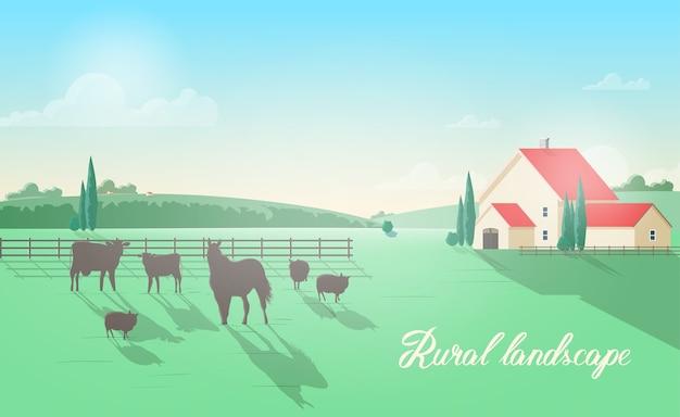 Wspaniały wiejski krajobraz ze zwierzętami domowymi pasącymi się na łące przed drewnianym płotem, budynek gospodarczy, zielone wzgórza