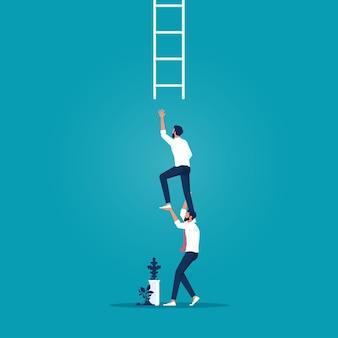 Współpracownik biznesmena wspiera swojego kolegę sięgającego po drabinę sukcesu