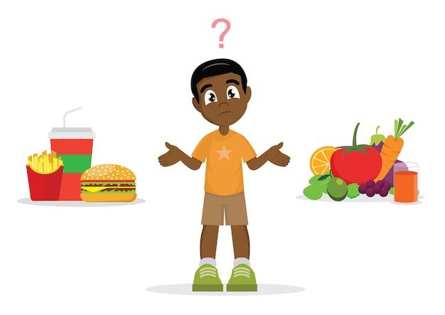 Wybór afrykańskiego chłopca. niezdrowe jedzenie lub zdrowa żywność.