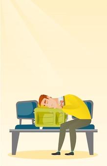 Wyczerpany mężczyzna śpi na walizce na lotnisku.