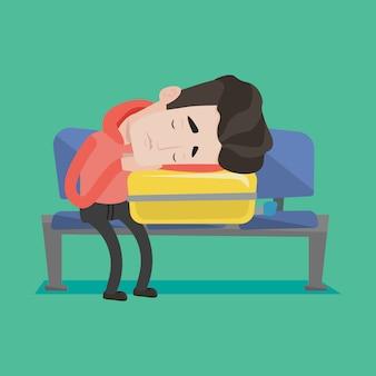 Wyczerpany mężczyzna śpi w walizce na lotnisku.