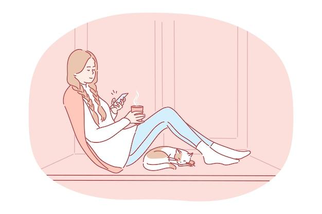 Wygodny relaks w domu ze smartfonem i gorącym napojem. postać z kreskówki młoda szczęśliwa dziewczyna siedzi na parapecie z herbatą, rozmawiając online na smartfonie, ciesząc się odpoczynkiem w domu w pobliżu śpiącego kota