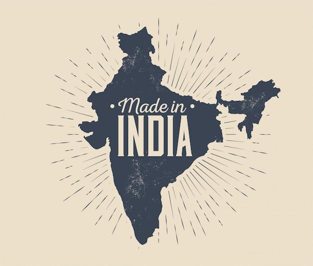 Wykonane w indiach odznaka lub szablon projektu etykiety lub logo z czarną sylwetką mapy indii z sunburst na białym tle na jasnym tle. ilustracja w stylu vintage