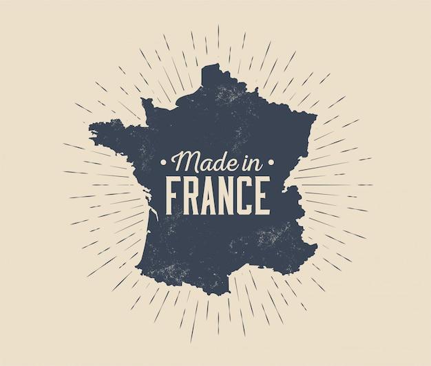 Wykonane we francji vintage czarno-biały wzór etykiety lub tagu lub logo lub znaczek z sylwetką mapy francji i sunburst na białym tle na jasnym tle. ilustracja