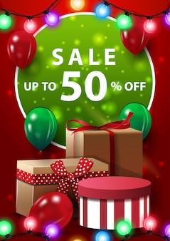 Wyprzedaż, do 50% zniżki, czerwony pionowy baner z balonami, girlandą i prezentami