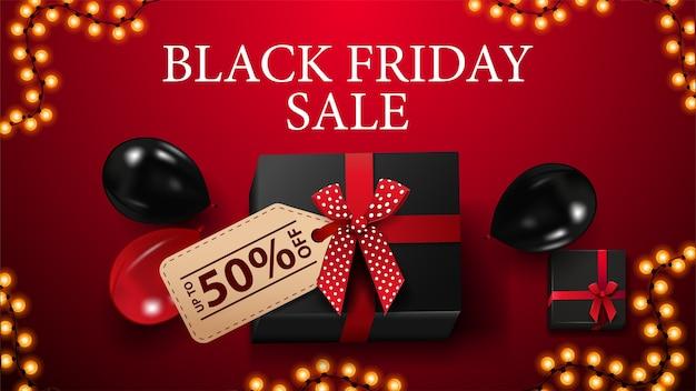 Wyprzedaż w czarny piątek, do 50% zniżki, czerwony baner rabatowy z czarnym prezentem z ceną z ofertą, ramka na girlandę oraz czerwono-czarne balony, widok z góry